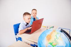 Two boys sit at the computer training school. The two boys are engaged for computer lessons in the school Stock Image