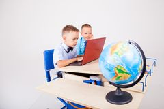 Two boys sit at the computer training school. The two boys are engaged for computer lessons in the school Royalty Free Stock Photo