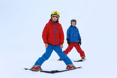 Two boys enjoying winter ski vacation. Two happy school boys, twin brothers in colorful snowsuits, having fun skiing in alpine mountains during snowy winter Royalty Free Stock Images