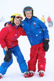 Two boys enjoying winter ski vacation. Two happy school boys, twin brothers in colorful snowsuits, having fun skiing in alpine mountains during snowy winter Stock Photos