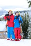 Two boys enjoying winter ski vacation. Two happy school boys, twin brothers in colorful snowsuits, having fun skiing in alpine mountains during snowy winter Royalty Free Stock Photography