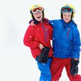 Two boys enjoying winter ski vacation. Two happy school boys, twin brothers in colorful snowsuits, having fun skiing in alpine mountains during snowy winter Stock Image