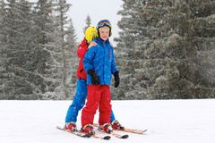 Two boys enjoying winter ski vacation. Two happy school boys, twin brothers in colorful snowsuits, having fun skiing in alpine mountains during snowy winter Royalty Free Stock Photo