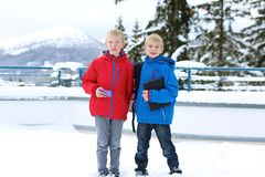 Two boys enjoying winter ski vacation. Two boys, twin brothers, in colorful warm coats playing outdoors in the snow Royalty Free Stock Image