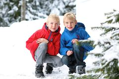 Two boys enjoying winter ski vacation. Two boys, twin brothers, in colorful warm coats playing outdoors in the snow Stock Photography