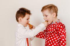 The two boys are fed each other pancakes. The holiday of Maslenitsa royalty free stock images