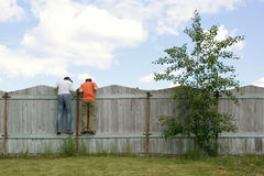 Two boys on the fence looking for smth. Photo of two boys on the fence looking for smth Royalty Free Stock Photography
