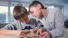 Two boys are finishing their wooden drone model stock footage