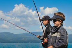 Two boys fishing with blue sky background. Royalty Free Stock Photography