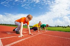 Two boys and girl on bended knee ready to run Stock Image