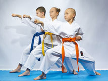 Two boys and a girl in karategi are hitting punch arm Royalty Free Stock Images