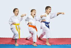 Two boys and a girl in karategi are hitting punch hand forward Royalty Free Stock Images