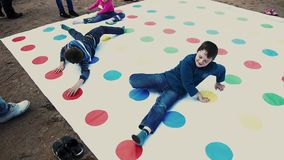 Two boys and girl play huge twister game on sand. Summer festival. Sunny day. Two boys and little girl play huge twister game on sand. Summer festival. Sunny stock video