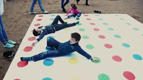 Two boys and girl play popular twister game on sand. Summer festival. Sunny day. Two boys and little girl play huge popular twister game on sand. Summer stock video footage