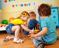 Two boys and girl playing with toy pyramid puzzle Stock Photos