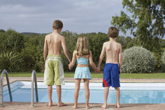 Two Boys And Girl At Pool's Edge Stock Photo