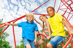 Two boys and girl sit on red ropes of playground Stock Photo