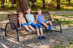 Two boys and a girl sitting on a bench in the summer. Three children royalty free stock photo