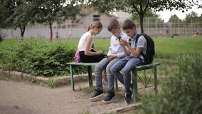 Two boys and girl use their phones during school breack. Cute boys sitting on the bench and play online games