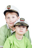 Two boys in green T-shirts and white sea peak-caps. With eyes looking somewhere upward stock images
