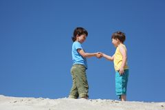 Two boys greet on sand stock photo