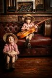 Brothers with guitar. Two boys with a guitar are playing at home in traveler. Childhood. Fantasy, imagination royalty free stock images