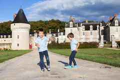 Two boys, happily playing after the rain on the driveway of Fren. Ch Gizeux castle, clear sky Stock Image