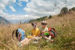 Two boys have got picnic in mountain field Stock Photos