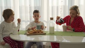 Two boys having breakfast in modern kitchen. Boy eat cookie with milk. White Table in Kitchen. Mother and two sons have. Breakfast. Cookies with milk stock video footage