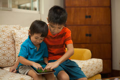 Two boys having fun with a digital tablet Royalty Free Stock Image