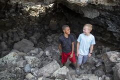 Free Two Boys Having Fun Hiking And Exploring In Some Lava Rock Caves Stock Photos - 182624313