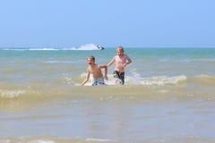 Two boys having fun in the sea stock photos