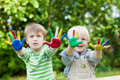 Two boys having fun and showing colorful hands Stock Image