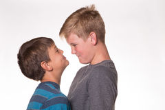 Two boys having a staring contest. Two boys staring each other down while laughing Stock Image