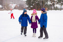Two boys helps girl learn to skate Royalty Free Stock Image