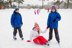 Two boys helps girl learn to skate Stock Images