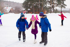 Two boys helps girl learn to skate Royalty Free Stock Photo