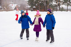 Two boys helps girl learn to skate Royalty Free Stock Images
