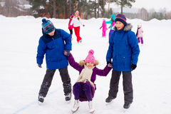 Two boys helps girl learn to skate Royalty Free Stock Photos
