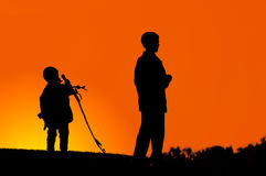 Two Boys on a Hill. Two boys standing on a hill dark silhouette over colorful digitally adjusted orange evening sky Stock Images