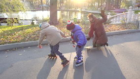Two boys and his mother funny ride on rollers and skateboard. In autumn park, slow motion 250 fps stock video