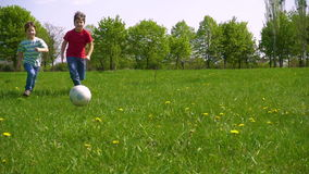 Two boys hit the ball on green meadow, slow motion. Two boys hit the ball on green meadow with dandelions, slow motion 250 fps stock video