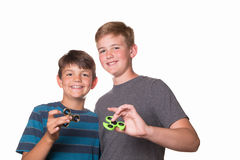 Two boys holding fidget spinners. And smiling at the camera stock photos
