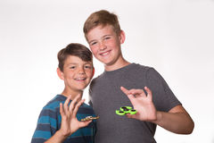 Two boys holding fidget spinners. And smiling at the camera Royalty Free Stock Photos
