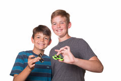Two boys holding fidget spinners. And smiling at the camera Stock Images