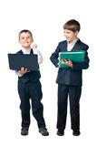Two boys holding laptop and folder. Two young boys dressed up in suits holding laptop and folder, isolated on white background Royalty Free Stock Photo