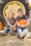 Two Boys Holding Pumpkins Talking and Sitting Against Tractor Ti Stock Photos