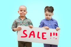 Two boys holding a sign. `SALE` in the hands. In light background royalty free stock images