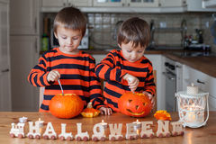 Two boys at home, preparing pumpkins for halloween Royalty Free Stock Images