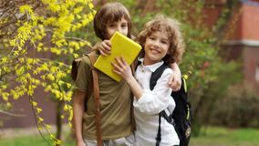 Two boys hug and look at the camera. School friends are laughing. Children have school bags behind them. Back to school. Children Day stock video footage
